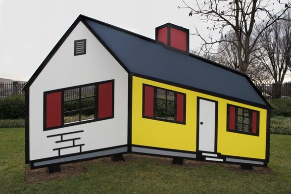 This sculpture is made up of panels and geometric shapes of vivid yellow, crimson red, daisy white, and slate gray, all outlined with bold, jet-black lines, to create a simplified, cartoon-like, single-story house. The sculpture sits slightly off the ground on four metal feet, and is displayed on a grassy lawn with an iron fence and trees in the background. One short end of the house faces us, to our left. The peaked wall is white and is pierced with a window divided into six empty panes, two across and three down, and flanked by red shutters. Above the window is a tall, rectangular air vent with six horizontal slats. Below the window a loose grid of three horizontal lines and four short, vertical lines suggest an abstracted brick pattern. The long side of the house moves away from us to our right. It has a red chimney at the center of the slate-gray roof. The wall of the front of the house is canary yellow. There is a white door at the middle and two more six-paned windows with red shutters to each side. Two shallow white steps leading down from the door are suggested by staggered, narrow rectangles. A dove-gray band runs along the bottom of both walls. All of the features, including the windows, shutters, door, chimney, roof, and gray band are outlined in black.