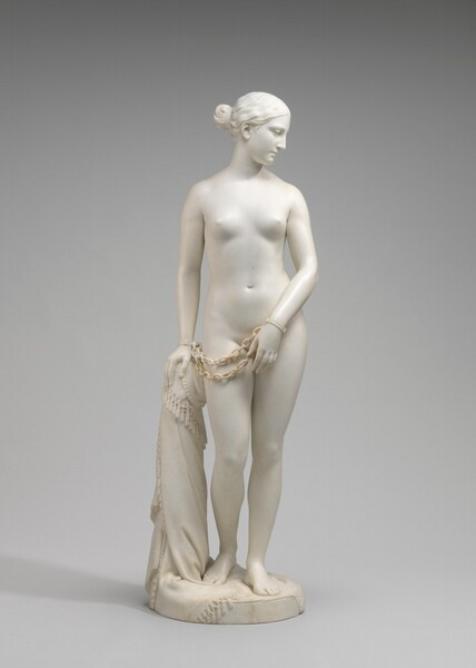 Carved from creamy white marble, a nude woman stands next to a hip-high support, perhaps a low post. Her weight rests on her left leg, on our right, and her other knee is bent. Her left arm, on our right, is angled in front of her body so her hand covers her groin. Her other hand, on our left, rests on the post. Chains hang from shackles encircling her wrists. She looks down to our right and is seen in profile in this photograph. Her wavy hair is tucked behind her ear and drawn back in a bun at the nape of her neck. The post is covered with a cloth that gathers around the top and spirals to the ground beneath her feet, the edge trimmed with tassels. A cross and medallion peek out from under the cloth near her hand. She stands on a circular base.