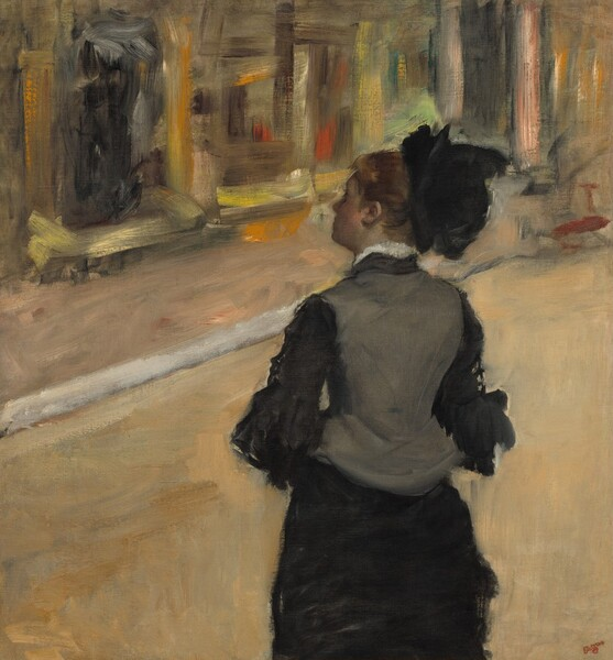 """Shown from about the hips up, a woman whose pale face is deep in shadow stands with her back to us, wearing a black and gray dress and hat, in front of a colorful but loosely painted, indistinct background in this nearly square painting. She stands just to our right of center with her elbows bent, perhaps to clasp her hands in front of her. Her head is turned slightly towards us so we see the line of her forehead, nose, and chin almost in profile facing our left. Her auburn hair seems to be pulled up under a black hat that sits on the back of her head. Her high-necked, charcoal-gray vest-like bodice has a line of white at the neck, suggesting lace or an undershirt. The bodice covers a black shirt with ruffles that fall at least to her elbows, and the long dress drapes close along the contours of her legs. She looks to the far wall, which is painted with sketchy, visible brushstrokes in marigold orange, lemon-lime green, brown, black, and pale yellow to create the impression of paintings in gold frames. The artist signed the painting in dark red in the lower right corner: """"Degas."""""""