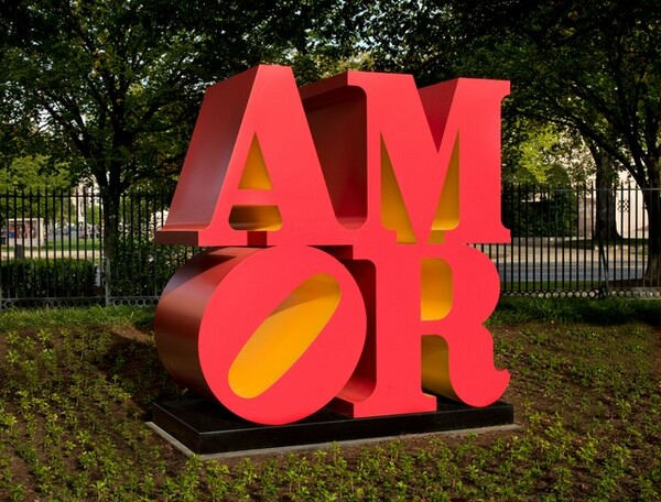Four deep, three-dimensional letters spell out the word AMOR in this sculpture, with the A and M stacked on top of the O and R to create a square on a low black platform. The letters are coral red with butter yellow undersides. The elongated, oval-shaped opening within the circular letter O is angled 45 degrees, towards the M at the upper right. We seem to stand slightly to the left in this photograph so we can see the deep sides of the letters. The sculpture is displayed out-of-doors with trees and a tall black fence in the background and plantings around the base. The trees and fence give it a sense of scale, and it looks like it reaches at least as high as the tall fence in the background.