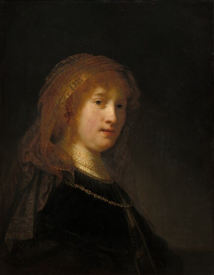 The light-skinned face of a young woman materializes from a deeply shadowed background in this vertical portrait. Shown from the waist up, her body is angled to our right and her face turns to look at us. She has gray eyes, a rounded nose, and her pink lips are slightly parted. A golden veil covers long strawberry blond hair and falls down over the shoulders of her dark dress. The dress has a high, white lace collar and a gold chain hangs over her shoulders and on her chest. Painted mostly with deep browns and earth tones, the light that falls on her face and hair creates an aura-like effect.