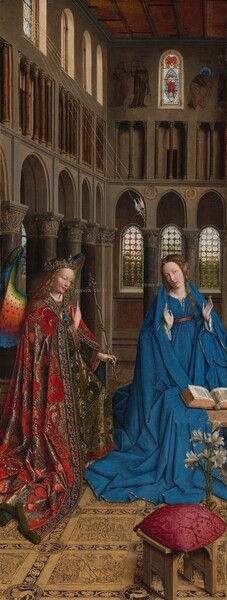 """Two people with pale, peach skin are situated in a church interior in this tall, narrow painting. The person to our left has long, blond, curly hair, smooth skin, and is smiling. The wings that indicate that this an angel are outlined in royal blue and blend down from blue to green to yellow to crimson. The angel holds their right hand up near their chest, the index finger subtly pointing upwards. Holding a long scepter in the other hand, the angel angles their body towards the woman to our right. The angel wears a gold jewel- and pearl-encrusted crown and a lavishly jeweled long, voluminous robe in a scarlet and shimmering gold brocade. The neck and along the opening down the front are lined with pearls and jewels. The angel looks towards the woman wearing a royal blue dress tied with a red belt at the high waist. Her long brown hair is tied back but one tendril falls over her left shoulder, on our right. She kneels facing us with her raised hands facing outward. Her head is tipped a bit to our left and she looks up and into the distance to our right with lips slightly parted. She kneels behind a book lying open on a low table. A vase of white lilies and a red cushion lies on the floor in front of the table, seeming close to us. The floor is decorated with stories set into square panels, as if inlaid with wood. The church behind and above the people has a row of tall, narrow arches with bull's-eye glass windows. An arcade of openings like windows supported by columns runs above the arches and sunlight comes in through arched windows under the flat wood ceiling. A white dove flies towards the woman on gold lines representing rays of light from a window at the upper left of the painting. Latin words painted in gold capital letters are exchanged between the people. The angel says, """"AVE GRA PLENA."""" The letters of the woman's response are painted upside down and backwards: """"ECCE ANCILLA DNI."""""""