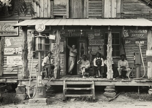 Country store on dirt road. Sunday afternoon. Note the kerosene pump on the right and the gasoline pump on the left. Rough, unfinished timber posts have been used as supports for porch roof. Negro men are sitting on the porch. Brother of store owner stands in doorway, Gordonton, North Carolina
