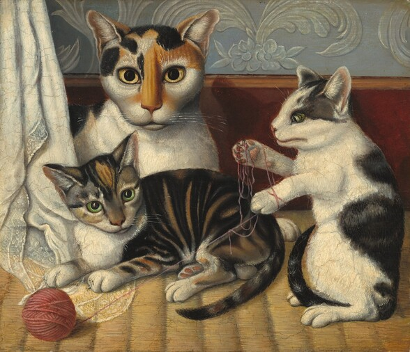 A short-haired calico cat and two kittens lie down or play with a ball of yarn in this horizontal painting. To our left, the largest cat has calico markings in honey brown and black over its face and along its spine, and the rest of its fur is white. Most of its body disappears behind a lace-trimmed cloth hanging along the left edge of the painting but it lies down so its chest faces us and it looks at us with piercing yellow eyes. One kitten lies in front of the larger cat so all four legs and its tail face us. It has caramel-brown, gray, and black stripes with white patches on its nose, chest, and paws. It looks off to our right with lime-green eyes. To our right, the other kitten rests up on its hind paws so its front paws are free to tangle the end of the carnation-pink yarn, which has rolled off a tidily wound ball to our left, in front of the other kitten. This kitten faces our left in profile and has white fur with flint-gray and black splotches along its spine, tail, and around its ears and eyes. The textured rug beneath the cats is straw yellow. A chestnut-brown baseboard spans the painting behind the cats, and the wall above is slate blue with stylized floral patterns in translucent white. The artist's precise brushstrokes are especially noticeable in the cats' fur and their shining whiskers.