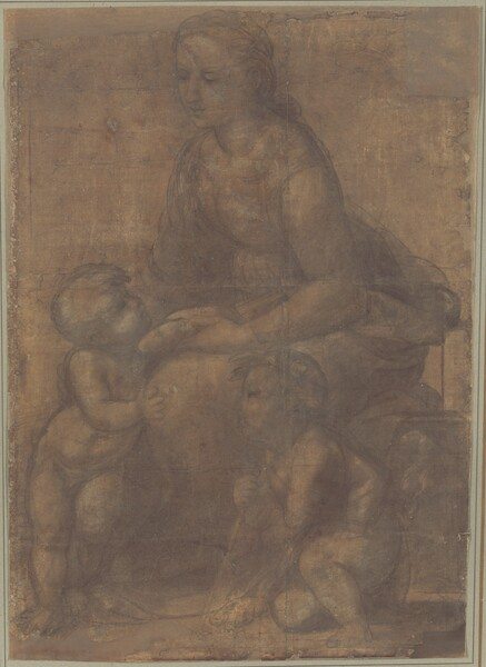 Drawn with gray chalk lines and smudges against dark tan paper, a woman sits facing to our left on a low wall, with two toddler-aged babies at her feet, filling this vertical drawing. Their bodies are outlined with smoke-gray lines and filled in with paler gray areas, giving the drawing an almost ghostly look. Both children have short hair and rounded, pudgy bodies. The woman has a subtly rounded figure, a straight nose, and smooth cheeks; her bow lips are closed. Her wavy hair is loosely pulled back and tied at the nape of her neck. Her dress, with a scooped neckline, is cinched at the waist before flaring into a voluminous skirt. She smiles down at the nude baby who stands to our left, looking up at her and leaning against her knees with his weight mostly on his right foot. Her left hand holds his left arm, which reaches across her lap toward a book she presses against her side with her left forearm. His right hand touches her left knee, nearest us, and her right hand passes behind him to caress his shoulders. The second child kneels in a crouch near the woman's legs, to our right. Leaning on a slender staff like a walking stick, he wears a garland of leaves in his hair and looks up toward the other boy. Chalk strokes and white highlights around his torso suggest he is wrapped in drapery. The curve of his back echoes the curve of the standing child's right hip and the arc of the woman's shoulders. Some details are difficult to make out because some of the charcoal-gray lines are loosely sketched and retraced. The corners and edges of the paper are chipped, revealing an underlying surface to which it is attached, and there are crease lines that suggest that the paper was likely folded in the past.