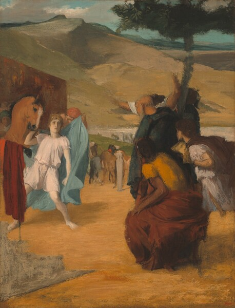 """Two groups of people seem to face off in this warm-toned vertical painting. On our left, a pale young man in a white tunic looks with eyes wide and lips parted at a group of three people on our right. His right hand, on our left, is raised to stroke the head of a reddish-brown horse at his right shoulder. He stands poised in a wide stance, knees bent, and he curls his left hand in a fist. Behind him, a man holds a swirling light blue cape ready to put on the youth. A mottled red wall forms a backdrop to this scene on our left. Less distinctly painted, the tight group gathered under a tree on our right stares back at the young man. The trio is made up of a balding, older man, a fair skinned boy also wearing a white tunic, and, closest to us, a dark-skinned woman wearing a bright orange shirt and a maroon skirt. Behind this group, a pair of pale raised arms suggests a fourth person, but the head has been painted over. The marigold-orange ground under the people reads as sand or dirt. In the center of the picture, beyond the people, a group of horses stands near a green bank by a river, its surface reflecting white, flanked by white buildings. Tan and olive-green slopes rise from the opposite riverbank under a watery blue sky with sweeping, cream-colored clouds along the top edge of the composition. The artist signed his name in red paint in the lower right corner: """"Degas."""""""