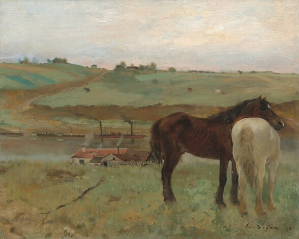 """Two horses, one dark brown and one creamy white, stand together to our right against a landscape with rolling, sage-green hills and a river or canal in this horizontal painting. Near us, facing our right in profile, the dark brown horse rests his head across the back of the creamy, white horse, who stands with its tail toward us. We and the horses seem to stand along the ridge of a grassy hill that dips beyond us to a waterway crossing the width of the canvas. Several buildings line the shore closer to us. At least one building has parchment-white walls and a red roof, and another has peanut-brown walls with a darker, chocolate-brown roof. More rooflines are nestled between, and gray smoke wafts from several chimneys. Long, low boats float near the opposite shore. The land rises in a hill across the water with more horses or other animals in the far pastures. The scene is loosely painted, and the background is the most indistinct, so some details are difficult to make out. Touches of brown and green suggest trees and perhaps more trees and buildings along the hill in the distance. The ivory-colored sky is touched with pale, petal pink and a hint of blue near the horizon. The artist signed and dated the work with dark paint in the lower right corner: """"E. Degas 71."""""""