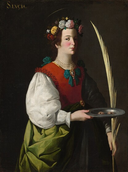 """Shown from about the hips up, a young woman with smooth, light skin, rosy cheeks, and dark brown hair stands in front of a dark background holding a pewter plate with two human eyes laid on it and a tall palm frond in this vertical painting. She stands with her body and face angled to our right but she looks to our left from the corners of her dark eyes, under dark eyebrows. She has a long, straight nose and her pink lips are closed. A strong light falls on the woman's face from our left, leaving the opposite half of her face in darkness. She wears a crown of ruby-red, buttercup-yellow, shell-pink, and white flowers on her head. A faint gold halo seems to catch the light above the flowers and then is swallowed in shadow. Her dress has a close-fitting, scarlet-red bodice over puffy white, long sleeves. A teal ribbon on her chest frames a gold and red brooch-like medallion. Three strings of white pearls encircle her neck above the neckline. Olive-green fabric that drapes over her left shoulder, farther from us, and around her waist is gathered with a gold brooch at her left hip. In her right hand, she holds a pewter plate with two lidded human eyes with dark pupils; they seem to look out at us. In her left hand, she holds a long yellow palm frond, which is bright against the dark brown background. The identify of the woman is inscribed in all capital, gold letters in the upper left corner """"S. Lucia."""""""