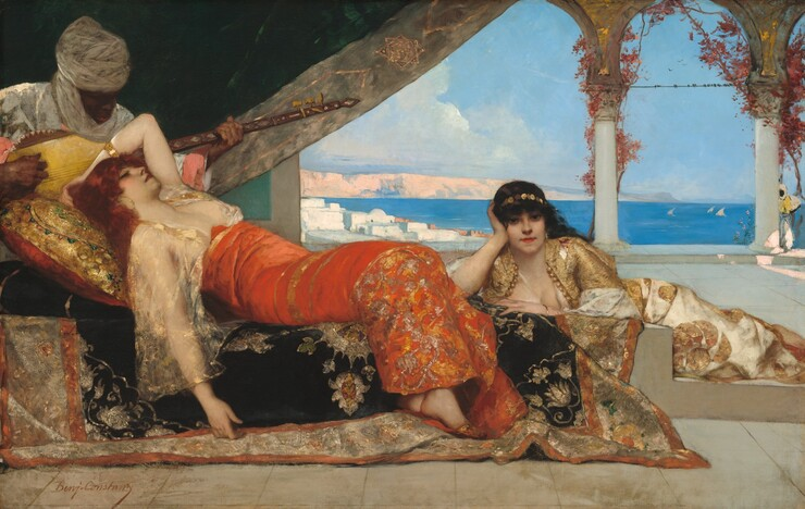 This horizontal painting shows a daylit covered terrace or open-air room with light sandstone colored floor tiles, where two women with pale ivory skin, wearing long dresses, lounge and recline on a rich black, gold, and copper colored carpet thrown over a low wall or ledge. The women are being entertained by a male musician, who is seated just behind them to the left. He has dark, mahogany-colored skin and wears a white turban that drapes around his neck and a white shirt with wide pink cuffs. His head is bent over a stringed instrument with a light-yellow rounded body and a long dark wooden neck. Behind and framing the musician, a dark green drapery with gold edging cuts across the top left corner of the painting and is drawn back to reveal a bright sea view beyond. Seeming close to us, one woman wears an orange-red dress with gold embroidery and a low-cut transparent ivory blouse that shows her pale skin beneath. She lounges on her back, head just beneath the figure of the musician, and body splayed out toward our right. Her eyes are half-closed, and her head rests on a large gold pillow with green and pink embroidery over which her long, dark red hair cascades. Her left arm is bent and thrown back behind her head while her right arm hangs limply toward the floor. Her extended legs are bent, and feet with red and gold pointed slippers emerge from the bottom of the dress. Staggered behind her to the right side of the picture, the other woman reclines in a gold and ivory dress with a filmy top and gold bolero jacket. She rests her head in her hand, propped up by a crooked elbow resting on a carpeted ledge, while her body extends toward our right. She gazes directly at us. She has dark, wavy hair that flows behind her shoulders and wears a gold headband with round, coin-like links. Beyond the group of three, another man stands in the far-right background in a corner of the terrace patio next to a pillar. His appearance is similar to that of the first man with dark, 