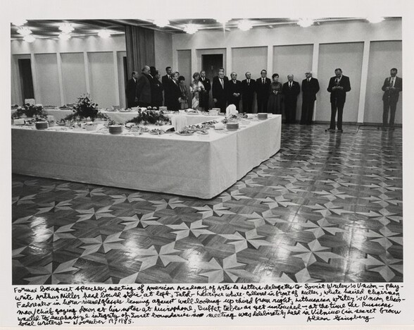 Formal banquet speeches, meeting of American Academy of Arts & Letters delegates to Soviet Writer's Union—Playwright Arthur Miller head bowed stoic at left, Jacob Laurence white-collard in front of Miller, white haired Chairman Fedorenko in horn-rimmed glasses leaning against wall looking up third from right, Lithuanian Writer's Union Chairman/Chief gazing down at his notes at microphone, Buffet table as yet untouched—at the time the Russians wanted to emphasize integrity of Society boundaries so meeting was deliberately held in Vilnius (in secret from local writers—November 19, 1985.