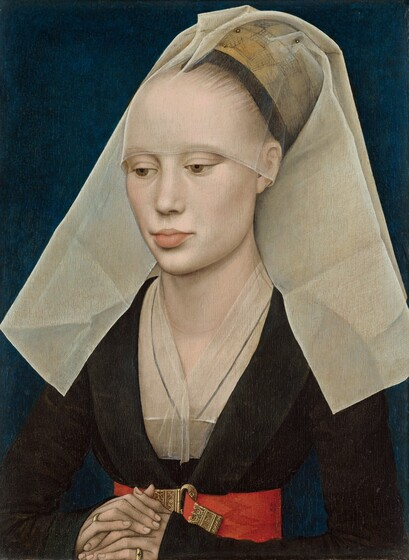 A woman with pale white skin and blonde hair is shown from the waist up in this vertical portrait. Her folded hands rest on the lower edge of the panel, suggesting that she sits just on the other side, close to us. A transparent white veil covers her blonde hair and falls in stiff, wide panes down in front of her shoulders. Her hair is pulled back behind a black ribbon over a high forehead. Her light brown eyes are downcast and she has a straight nose and full, pale pink lips. Her chest is covered by another veil and is tucked into the deep V-neck of her long-sleeved, black dress. A wide scarlet belt adorned with an ornately filigreed gold belt buckle encircles her narrow waist. Her porcelain skin, white veils, and red belt contrast sharply with her velvety black dress and the dark pine green of the background.