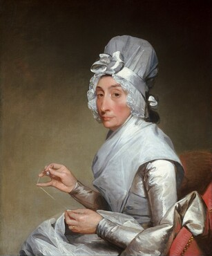 Seen from the lap up, a woman with pale skin wearing a white satin dress and tall white bonnet sits sewing with her body facing our left in this vertical portrait painting. She turns her head to look directly at us from under slightly raised eyebrows with heavy-lidded, almond-shaped dark brown eyes. She has a long, sharp nose and her high cheekbones are lightly flushed. Her thin lips seem pressed together with the corners pulled back, and her mouth is framed by vertical wrinkles along her chin. A bonnet of sheer  white fabric is secured around her head by a white silk ribbon tied into a four-loop bow above her forehead. The bonnet is pleated to create ruffles that frame her face. The woman pinches threaded sewing needle between her right thumb and index finger, farther from us, while holding the thread taunt with her outstretched pinky. Light catches a pearl-like object near her thumb, but on closer inspection it might be a thimble she wears on her middle finger. The remainder of the thread is secured by her left index finger and thumb as is the fabric she stitches. A gold wedding band glistens on her left ring finger. The crisp fabric of her dress looks white in the light and the shadows are a silvery pale gray. The long sleeves fit closely along her arms and more fabric, perhaps of the skirt, billows up beside her over the arm of the chair. A piece of gauzy white cloth drapes over the woman's neck and over her shoulders, and may be tied around her torso. She sits in a dusky rose-pink upholstered chair lined with brass nail heads against a smoky taupe background.
