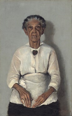 "In this vertical portrait, an elderly woman with brown skin, wearing a blouse, apron, and skirt is painted with a limited palette of grays, browns, black, and whites. Her head, torso, and lap nearly fill the composition. She is shown straight-backed against a neutral gray background, facing and looking at us with her hands resting in her lap. Her wavy, iron-gray hair is parted in the center and pulled back from her face. Her eyebrows are slightly raised and her face is deeply lined down her cheeks and around her mouth. She wears a heart-shaped brooch with a red stone at its center at her neck and a gold band on her left ring finger. The light coming from our left casts a shadow against the wall to our right. The artist signed and dated the painting in the lower right corner: ""A.J. MOTLEY. JR. 1922."""