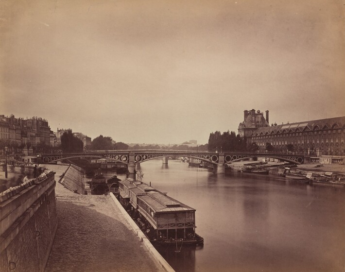 We seem to stand on a paved walkway running alongside a river as we look across the placid water towards a bridge spanning two banks of an elegant city in this horizontal sepia-toned photograph. Printed in warm, rich tones of brown and ivory, the horizon line comes almost halfway up the composition. A few low, blocky barges and boats line the river in front of us and along the opposite bank. The span of the bridge ahead of us is supported by three shallow arches with descending circles where the arches meet the pillars and flat top of the bridge deck. A long building with rows of windows leading to a high peaked roof runs parallel to the river to our right. More buildings face the river to our left in the distance. A few shadowy forms near the left edge of the photograph, close to us, were created as people moved during the long exposure time needed for the image.