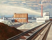 """This nearly square painting shows an industrial area with buildings, storage silos, a smokestack, and railroad tracks, but no people. A mound of brown dirt or other material is in shadow in the lower left corner of the painting next to the railroad tracks that extend diagonally from the lower center of the painting into the distance to our right. The tracks end at a white building with staggered gray rooflines to our right in the middle distance. A tall terracotta colored smokestack rises beyond the white building with smoke pouring out of the top and blending into the clouds above. To the left of center and slightly closer to us is a row of ten interlocking, coral-colored silos. Our view is cut off by a row of long white and gray warehouses in the distance between the silos and smokestack. Piles of white material, perhaps in unseen bins, fill the area between the silos and the railroad tracks in the foreground. The artist signed and dated the work with brown paint in the lower right corner: """"Sheeler 31."""""""