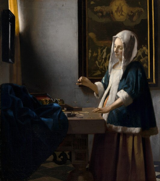 In this vertical painting, a woman stands near the corner of a dimly lit room, facing our left in profile looking down at a balance she holds suspended in her right hand over a wooden table. She wears a peacock-blue velvet jacket with a white hood and fur lining, and a voluminous mustard-yellow skirt. Light coming in through a window at the upper left corner, which is at least partially covered by a canary yellow curtain, falls on the creamy white skin of her face and hands, and highlights the white trim of her garment. Her left hand, closer to us, rests on the edge of the table near two open boxes, and a blue cloth is bunched at the back of the table to our left. Gold chains and pearl strands drape over the edge of one box. The woman stands in front of a framed painting. Much of the detail is lost in shadow but at the top center of the painting, a person surrounded by a golden halo floats in the sky with both arms raised, and is flanked by people encased within a bank of clouds. Nude people on the ground below, seen to either side of the woman, writhe, twist, and point upwards.