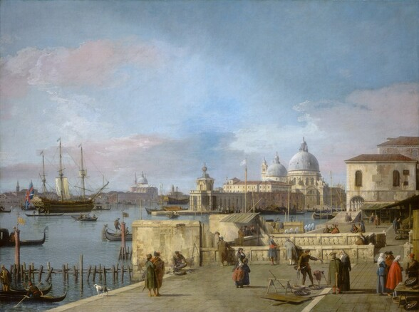 We seem to be slightly elevated, looking down onto a port-side town along a canal, with a church across the water from us in this horizontal landscape painting. The bright blue sky with billowing white, pink, and gray clouds fills the top two thirds of the painting. Below, a three-masted ship with all but one sail furled is surrounded by a couple dozen black long, low boats, gondolas, and one or two other sailboats. People stand and walk mostly in pairs and trios along the stone walkway under us, which extends into the distance to our right. The women all wear long dresses and most of the men wear suits with knee-length jackets with tails or capes, and hats. The clothing is painted in shades of brick red and terracotta, pine green, royal blue, and gray. The walkway is interrupted by two low walls that partition off an area near us. The angled roofs of stalls line the walkway in the farther distance before it is again interrupted, this time by a two-story, cream-colored building. The walkway seems to continue as a narrower path under an arched arcade on the lower level of that building, alongside the water. Across the canal from us, a cluster of ivory-colored buildings includes a building with two stone blue domes. More buildings extend into the deep distance to our left.