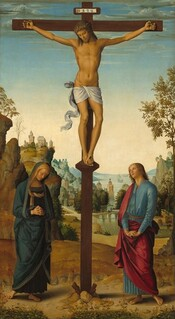 """A man hangs from a wooden cross at the top center of this vertical painting, with a woman standing at the foot of the cross to our left and a man to our right, all in front of a deep landscape with a town and mountains along a river. All the people have light skin. The feet of the man on the cross, Jesus, line up with the tops of the heads of the people standing below. Jesus hangs by a nail driven through each palm, and his overlapping feet are nailed into a short platform that angles downwards. He has shoulder-length brown hair and a short brown beard. His head tips forward and his eyes are downcast or closed. He has a straight nose, high cheekbones, and his lips are closed. Blood trickles down his forehead from a ring of thorns around his head, from the nails in his hands and feet, and from a short gash over his right ribs, on our left. A white loincloth is wrapped around his hips and the end of it flutters as if in a breeze to our left. The man's body is lean but muscular. A slip of paper with the letters """"INRI"""" has been affixed to a small panel on the cross above Jesus's head. Below and to our left of the cross, a woman stands with her head bowed, looking down at the ground with her hands clasped in prayer. Her hair is covered with a tan-colored veil and she wears a gold-edged, navy blue robe that covers her head and body. She and the clean-shaven, blond man standing to our right of the cross both have bare feet. The man looks up at the cross with his lips parted. His fingers are intertwined and then flipped, palms-down, with his arms straight. His raspberry pink robe falls over one shoulder and around his hips, over a topaz-blue, ankle-length tunic. The dirt-packed ground on which they stand is lined along the bottom edge of the panel with plants and flowers. The golden-brown land dips beyond the people, leading down to a river that winds into the distance. A castle-like structure perches on cliff-like outcroppings high along the left edge of the painting and b"""