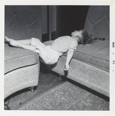 Untitled (Girl lying across two couches)