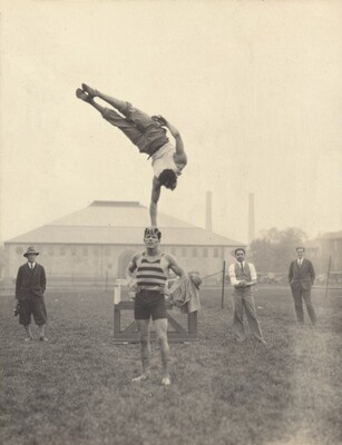 Untitled (Man balanced in one-armed handstand on top of another man's head)