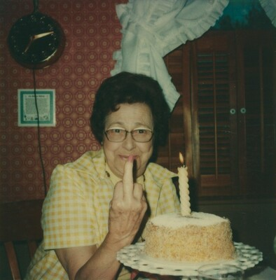 Untitled (Woman giving the finger with birthday cake)