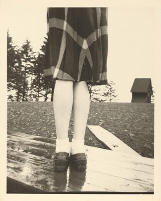 Untitled (Plaid skirt and legs on wood table)