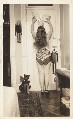 Untitled (Woman posed from behind against door with hanging skeleton)