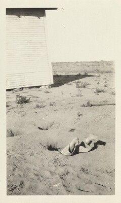 Untitled (Boy's feet sticking out of sand)