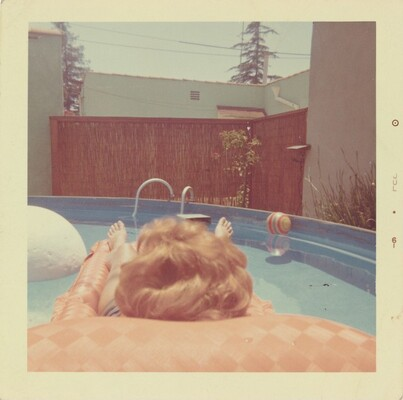 Untitled (Woman floating on raft in pool)