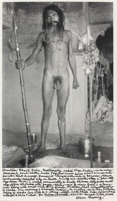 Shambhu Bharti Baba, traditionally naked Naga Sadhu in sandy basement porch-shelter under Pilgrims' Guest-house above ancient Manikarnika Ghat burning-grounds at Ganges waterside in Benares, oldest cintinuously inhabited city on Earth. During six-months stay a few alleys down-river, I visited occasionally to smoke chilams, clay pipes as at [?] edge of fire-pit, packed with ganja-tobacco mix & share Baba's silence vow along with small circle of his friends, devotees, local schoolteachers & clerks. One morning I brought camera, he invited me to take pictures rising to disrobe loin-cloth & G-string, stood nude beside Naga spear, brass waterpot & Shiva Trident. See Indian Journals [title underlined], 1970, p.130. December 18, 1962, 10:30 AM.