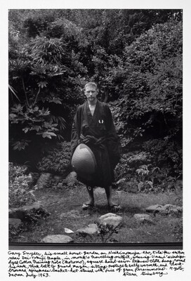 Gary Snyder, his small house-garden on Nishinomiya-cho, Kita-ku section near Dai-tokuji temple, in monk's travelling outfit, wearing Unsui's indigo-dyed cotton training robe (koromo), square handsewn Rakusu cloth hung round his neck, thick belt to guard zazen sitting posture & belly warmth, and dark-browned Ajirokasa basket-hat stained with juice of green persimmons. Kyoto, Japan July 1963.