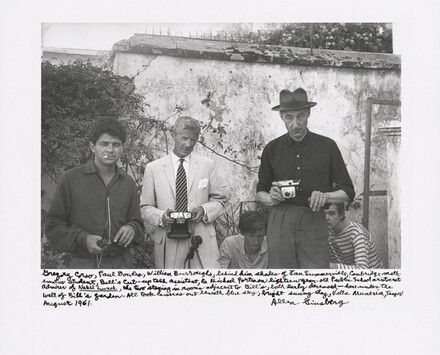 Gregory Corso, Paul Bowles, William Burroughs, behind him shades of Ian Summerville, Cambridge mathematics student, Bill's cut-up tech assistant, and Michael Portman, eighteen-year-old Public School aristocrat admirer of Naked Lunch, the two staying in rooms adjacent to Bill's, both early deceased — here under the wall of Bill's garden. All took cameras out beneath blue sky, bright sunny day, Villa Muniria, Tangier August 1961.