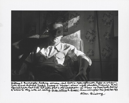 William S. Burroughs looking serious, sad lover's eyes, afternoon light in window, cover of just-published Junkie propped in shadow above right shoulder, Japanese kite against Lower East Side hot water flat's old wallpaper. He'd come up from South America & Mexico to stay with me editing Yage Letters and Queer manuscripts. New York Fall 1953.