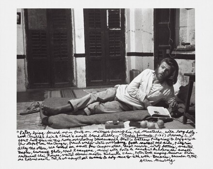 """Peter lying dressed up in pants on mattress picking his red moustache, with long hollywood Christlike hair & Christ's small beard stubble — "" (Indian Journals, p. 132) Orlovsky & I spent half year in this room overlooking Dasasumedh Ghat's bathers pilgrims & beggars a few steps from the Ganges, french window slats overlooking food market one side, pilgrim alley the other. We cooked on small gas camper stove, kept records, wrote letters, visited temples, burning ghats, read Ramayana, mixed with poets  & sanskrit Achkans in small restaurant chai houses, visited shenai master Bichmulla Khan, Peter took singing lessons from one Rabmdranath Pal, & we sought out swamis & holy men to talk with. Benares, December 19, 1962."