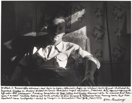 William S. Burroughs serious, sad lover's eyes, afternoon light in window, cover of just-published Ace Paperback Junkie in shadow propped on couch-back above right shoulder. Japanese kite against old hot-water-flat wallpaper. Finishing compilation of Yage Letters and Queer manuscript he visioned first Inter-zone Market routines looking out South window at fire escapes & clotheslines criss-crossing Lower East Side apartment house courtyards--sailed to Tangier in December. New York, Fall 1953.