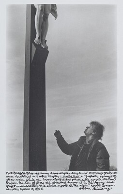"""Poet Gregory Corso addressing cross atop the Grey Nuns' Orphanage grotto Kerouac immortalized in book 4 Chapter 1, Doctor Sax, a """"gigantic pyramid of steps upon which the Cross itself poked phallically up with its poor burden the Son of Man all skewered across it in his Agony and fright – undoubtedly this statue moved in the night."""" Lowell, Massachusetts, March 17, 1986."""