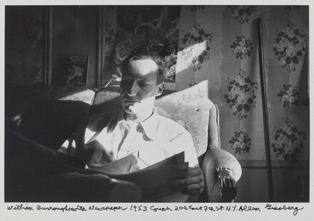 Williams Burroughs with a Newspaper 1953 couch 206 East 7th St. N.Y.