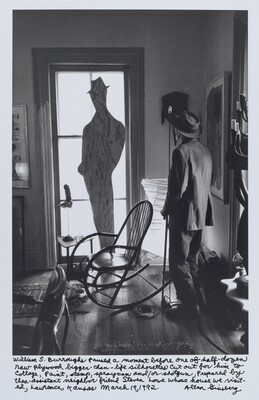 William S. Burroughs paused a moment before one of half-dozen raw plywood bigger-than-life silhouettes cut out for him to collage, paint, stamp, spraycan and/or shotgun, Prepared by then-assistant neighbor friend Steven Lowe whose house we visited, Lawrence, Kansas March 19, 1992.