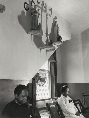 Washington, D.C. Sitting beneath the emblem of the crucifixion of Jesus on Calvary. Two members of the St. Martin's Spiritual Church listen and pray.