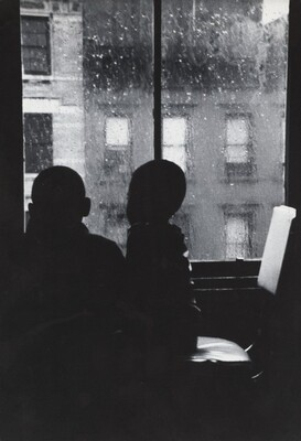 Two Boys Looking Out a Window on a Rainy Day