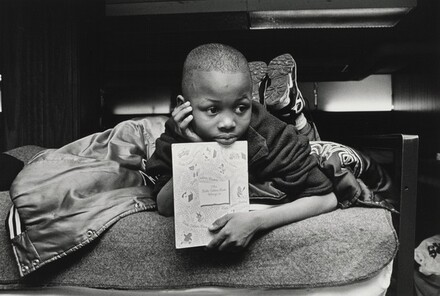 Margie's son, Jamont, 9, watches from his perch on a bunk bed as his mother chooses a dress for her job-training class. In the United States an alarming number of children are homeless. Olive Branch Mission, Chicago.