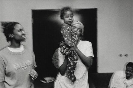 A young woman holds her baby brother high. Olive Branch Mission, Chicago.