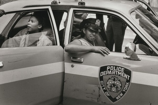 On a warm July day neighborhood children play in a patrol car, New York City