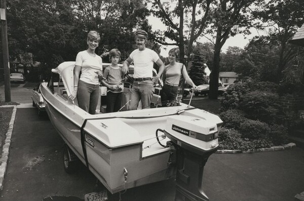 A police officer and family pose in their fishing boat, parked in their yard, Long Island, New York