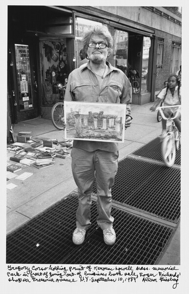 Gregory Corso holding print of Kerouac Lowell Mass. Memorial Park in front of going-out-of-business book sale, Roger Richards' shop on Greenwich Avenue N.Y. September 10, 1989