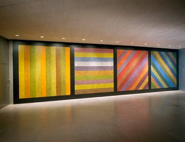 Wall Drawing No. 681 C / A wall divided vertically into four equal squares separated and bordered by black bands. Within each square, bands in one of four directions, each with color ink washes superimposed.