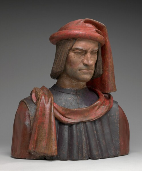 This three-dimensional, painted terracotta portrait shows the head, shoulders, and chest of Lorenzo de' Medici. His face and body are angled slightly to our right in this photograph and he seems to look down his crooked nose. He has peach colored skin, which is lightly shadowed around his chin. His thin lips are set in a resolute line and his brow is furrowed low above his eyes. Chin-length brown hair hangs straight down the sides of his face. His garment has vermillion red sleeves under a navy blue tunic, and he wears a red headdress that hangs down to his shoulder over his left ear, on our right. A red scarf drapes across his chest and the end hangs on his chest on our left. Paint losses on the surface of the sculpture allow the brown terracotta to show through in some areas.