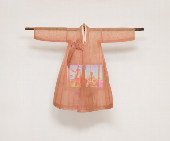 A lightweight, sheer, coral-peach robe hangs from a wooden dowel over a color television screen in this sculptural piece. The robe has long sleeves extending horizontally along the dowel, which extends a bit past the cuffs. The robe has a narrow, cream-white collar and ties to one side over the chest. It flares slightly below the arms, creating a bell shape. The rectangular video screen that hangs within is partially obscured, but looks like at least two people in a brightly colored setting.