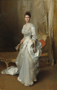 """A woman with pale white skin and dark brown hair, wearing a long sleeved, floor-length white satin dress, stands facing and looking out at us in front of a chaise lounge in a room hung with gold drapery in this vertical, full-length portrait. The woman's body is angled slightly to our left and her hair is piled on top of her head. She has dark eyes, a straight nose, and her rose-red lips are closed. She wears pearl earrings, a string of pearls at her throat, and a brooch with two large pearls at her chest. The deep V-neck of her dress is edged with layers of sheer fabric that drapes over her shoulders. Some areas of the dress are loosely painted but gives the impression of lace edging along the collar and bows down the front of the bodice and at the elbows of the half sleeves. The train of the dress bunches around her feet behind her to our left and is either gathered at her left hip, on our right, or her dress has a voluminous bustle there. She holds a partially open fan in her right hand, on our left, and black opera glasses in the opposite hand, nestled into the bustle. She wears a gold bangle on her left wrist and a glittering blue stone ring on the ring finger of that hand. She stands before a chaise longue—a half-chair, half sofa—edged with gold and upholstered with gold fabric. A swath of golden ivory fabric hangs behind her like a curtain. The artist signed and dated the work in the lower right corner in dark brown paint: """"John S. Sargent 1883."""""""