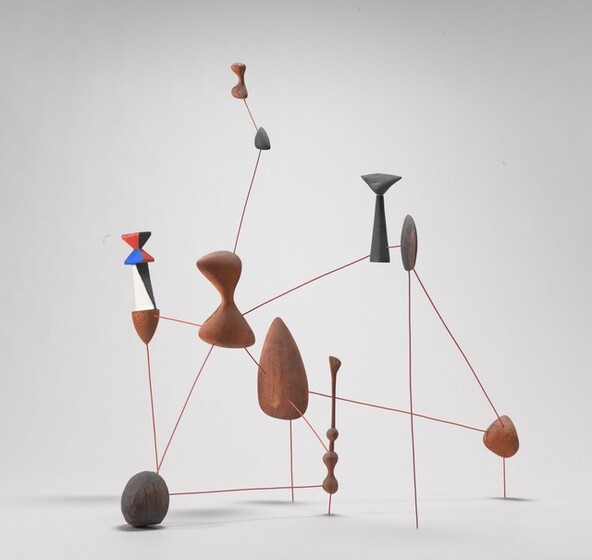 This sculpture is made up of ten shapes connected with rigid, straight brown wire to create an interlocking, web-like formation that rests on the floor. Five of the shapes appear to be raw wood and the other five are painted. Four of the painted shapes are dark gray. The fifth painted piece, at the upper left in this photograph, has a wooden cone-shaped tip pointing downwards beneath a black and white mid-section and an angular, hourglass shaped tail painted in triangular blocks of red, blue, and black. The other wooden and painted shapes range in size and form, with an almond-shaped piece at the center, rounded pieces throughout, and two rounded hour-glass shaped pieces near the upper left.